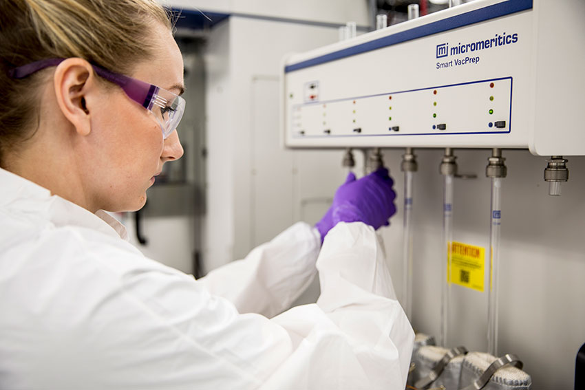 A young woman in a lab coat, protective glasses, and lab gloves adjusts the settings on a piece of scientific equipment.