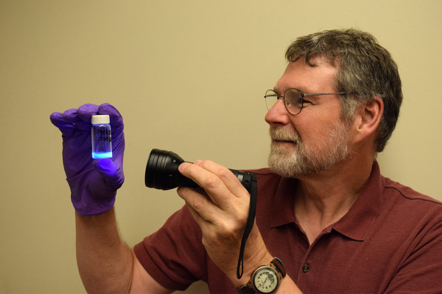 A man wearing glasses shines an ultraviolet flashlight onto a small container; the contents glow blue.