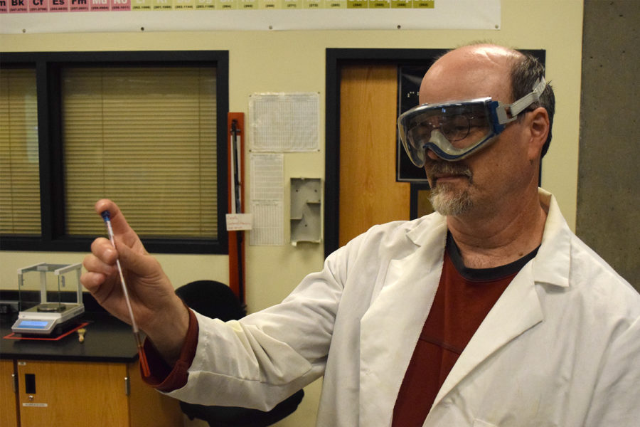 A man in a lab coat and goggles holds a test tube containing a red liquid.