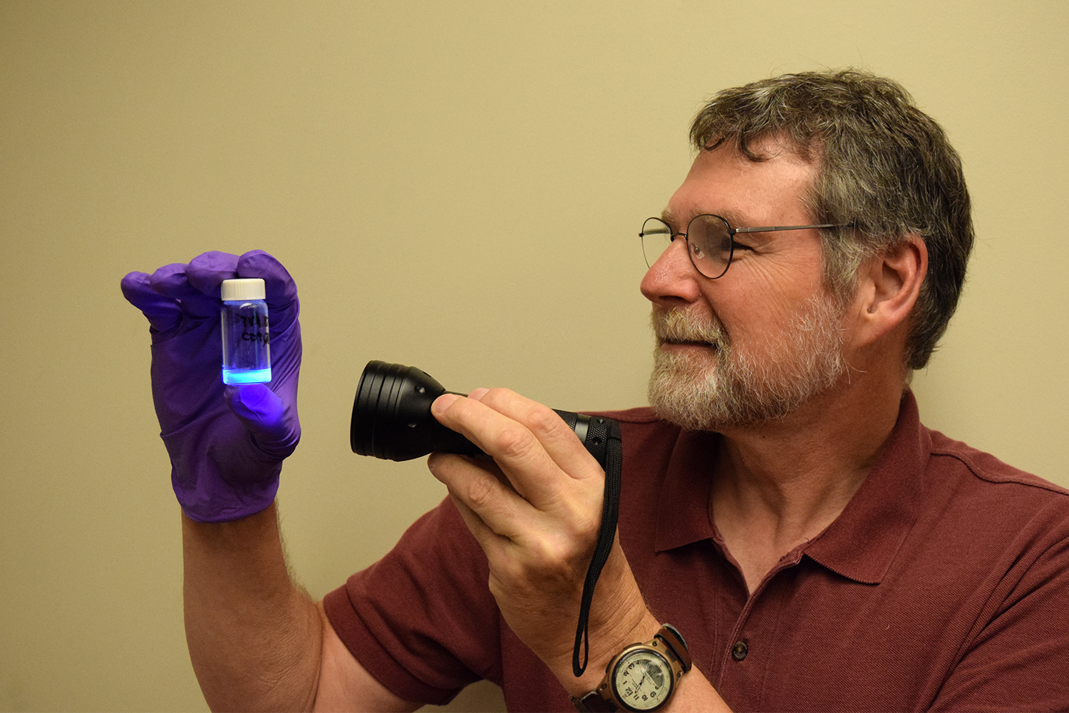A bearded man holds a flashlight to a small vial with glowing blue contents.