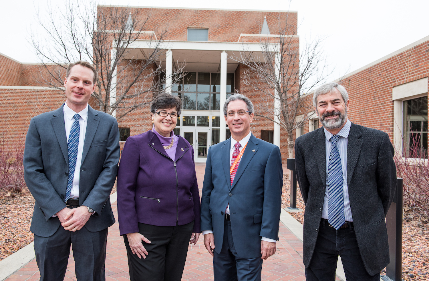 A woman in a purple jacket and sweater and three men in suits pose in front of a brick building.
