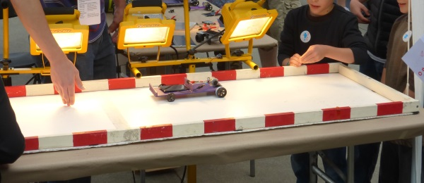 Solar car on a table top race track with worklights.