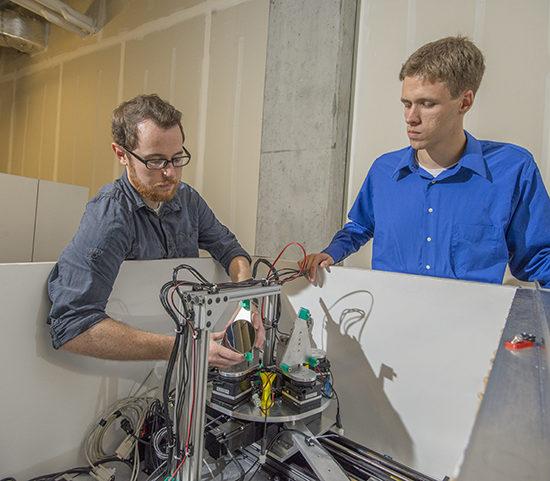 Two CEI Graduate Fellows examine a scientific instrument.