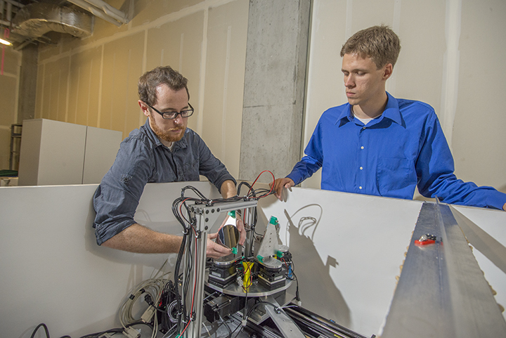 Two CEI Graduate Fellows examine a scientific instrument.