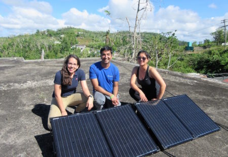 Ahumada, Keerthisinghe, and Kang with recently-installed solar cells on the roof of the community center.