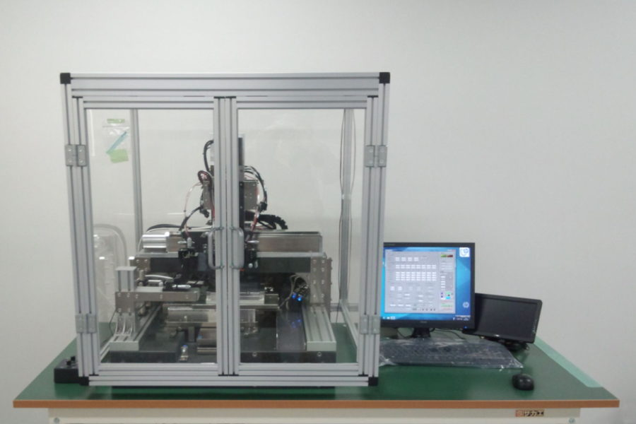 Printing machinery enclosed in a glass box next to a desktop computer.