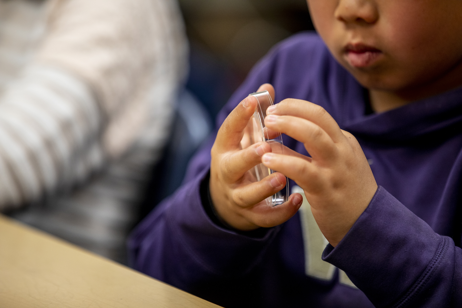 A young student in a University of Washington hoodie assembles a solar spinner from a small panel and a petri dish.