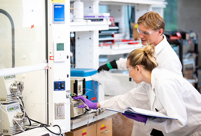 A young woman and man in lab coats and protective glasses operating lab machinery.