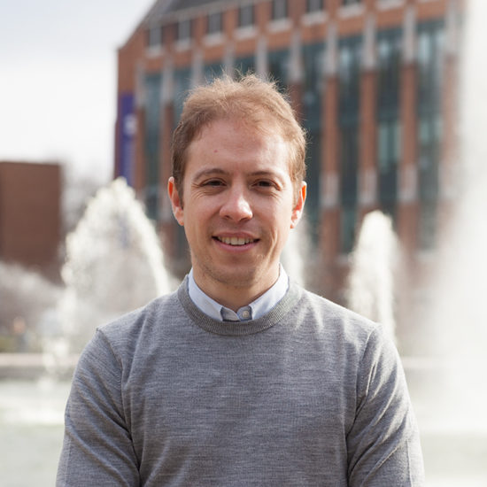 A man in a collared shirt and sweater poses in front of a fountain.