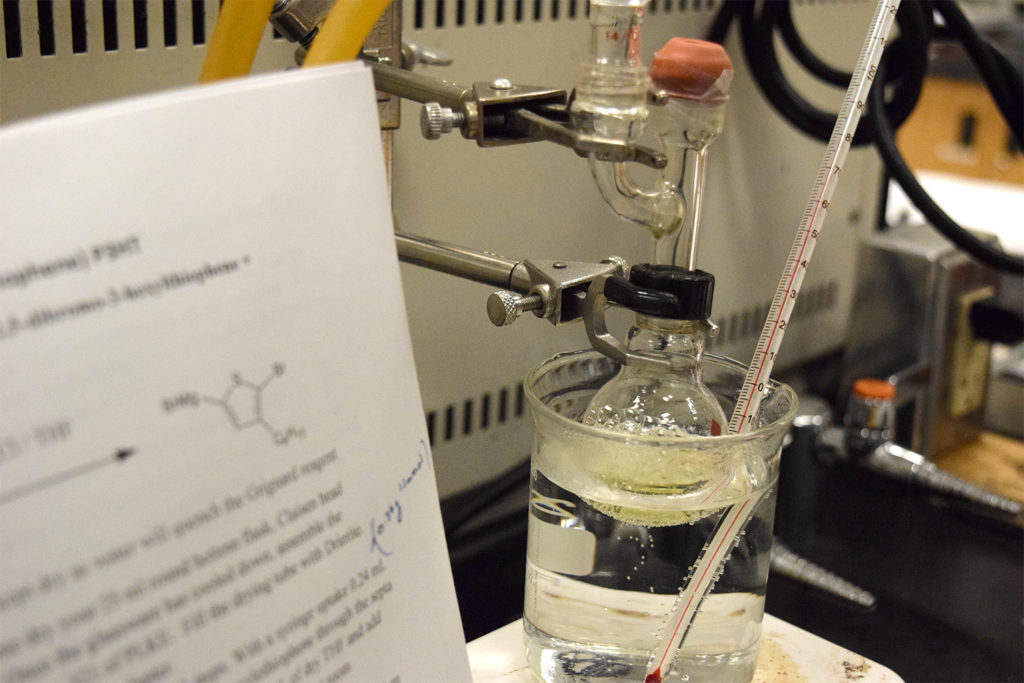 Close-up of a chemical reaction, with a white paper that describes the reaction in the foreground.