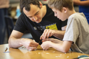 A young man with a black t-shirt and a yellow nametag sits at a table with a young student. The two are working together to assemble a small solar spinner from a petri dish.