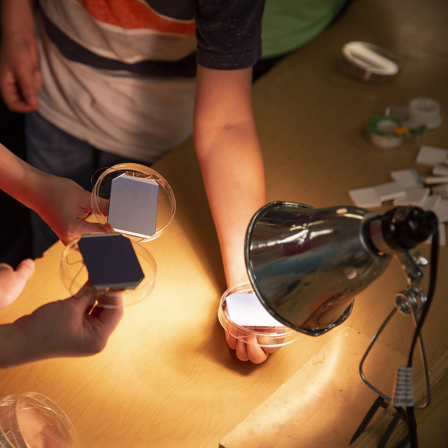 Two students hold their solar spinners - solar panels glued to petri dish lids - underneath a high-intensity lamp.